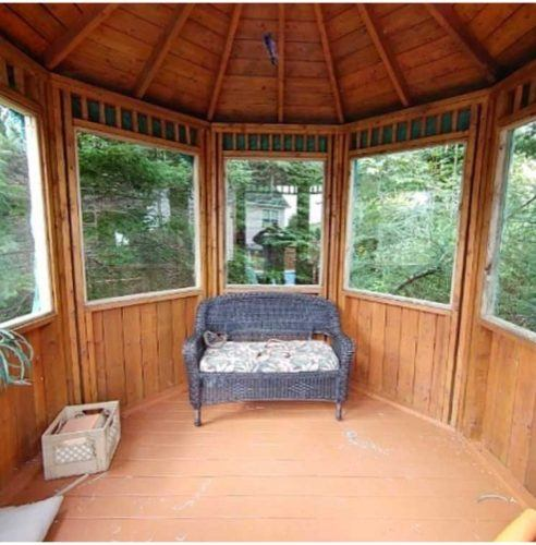 inside of a wooden gazebo with glass windows and a grey couch in the middle